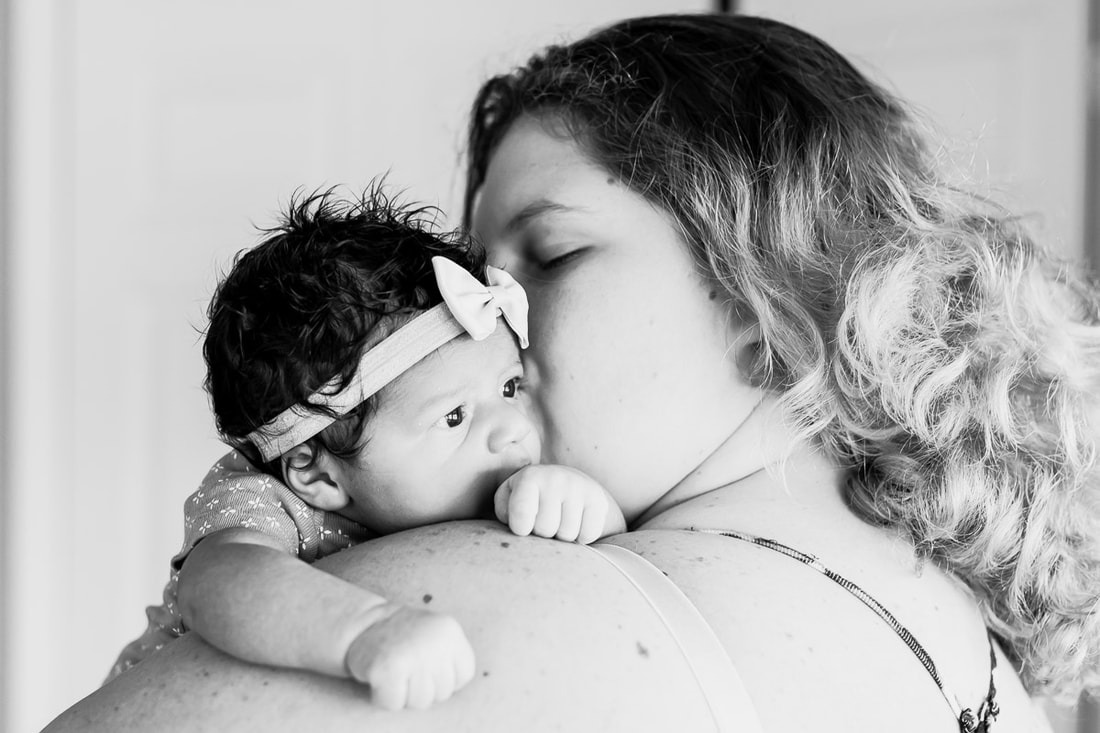 Black and white close up of mom kissing newborn holding over shoulder, Bradenton, Florida