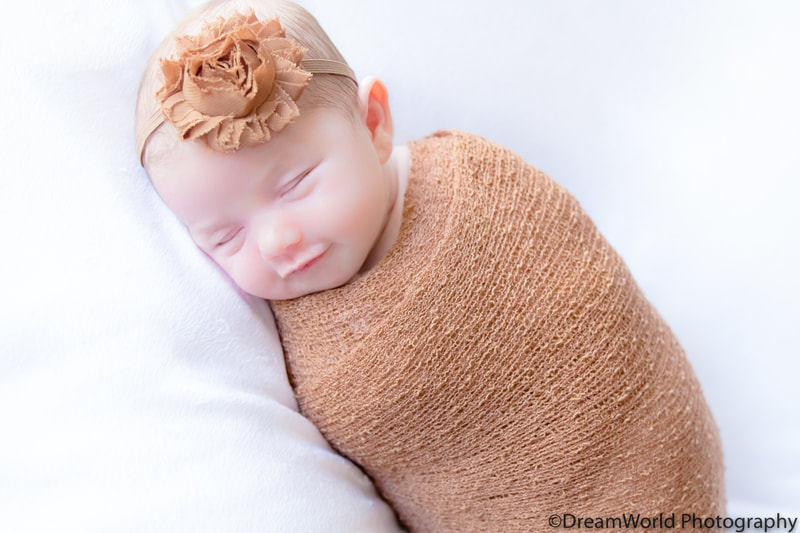 Sleeping baby posed in brown wrap