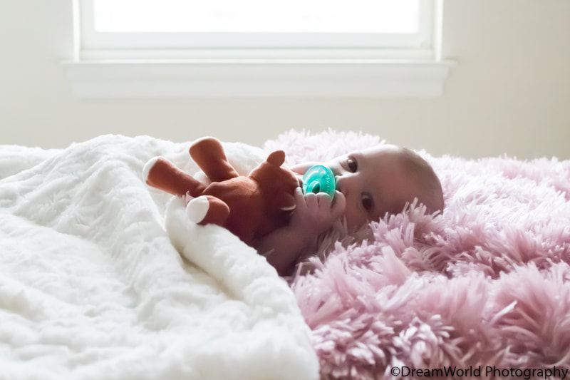 Lifestyle baby laying on bed with pacifier