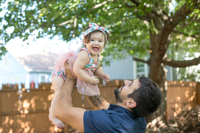 Father holding laughing daughter up in air outside