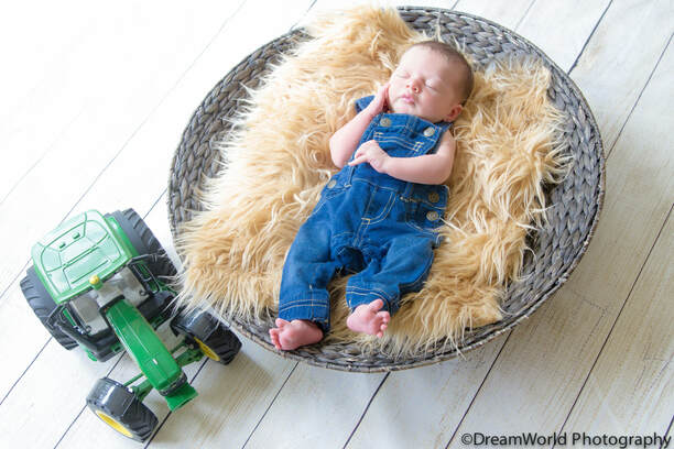 Baby in overalls with John Deere tractor