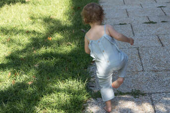Lifestyle, family, toddler girl walking holding one leg up, outdoors