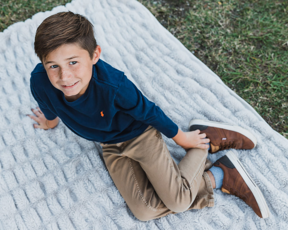 8 year old sitting on ground on blanket looking up at camera, Celery Fields, Sarasota, Florida