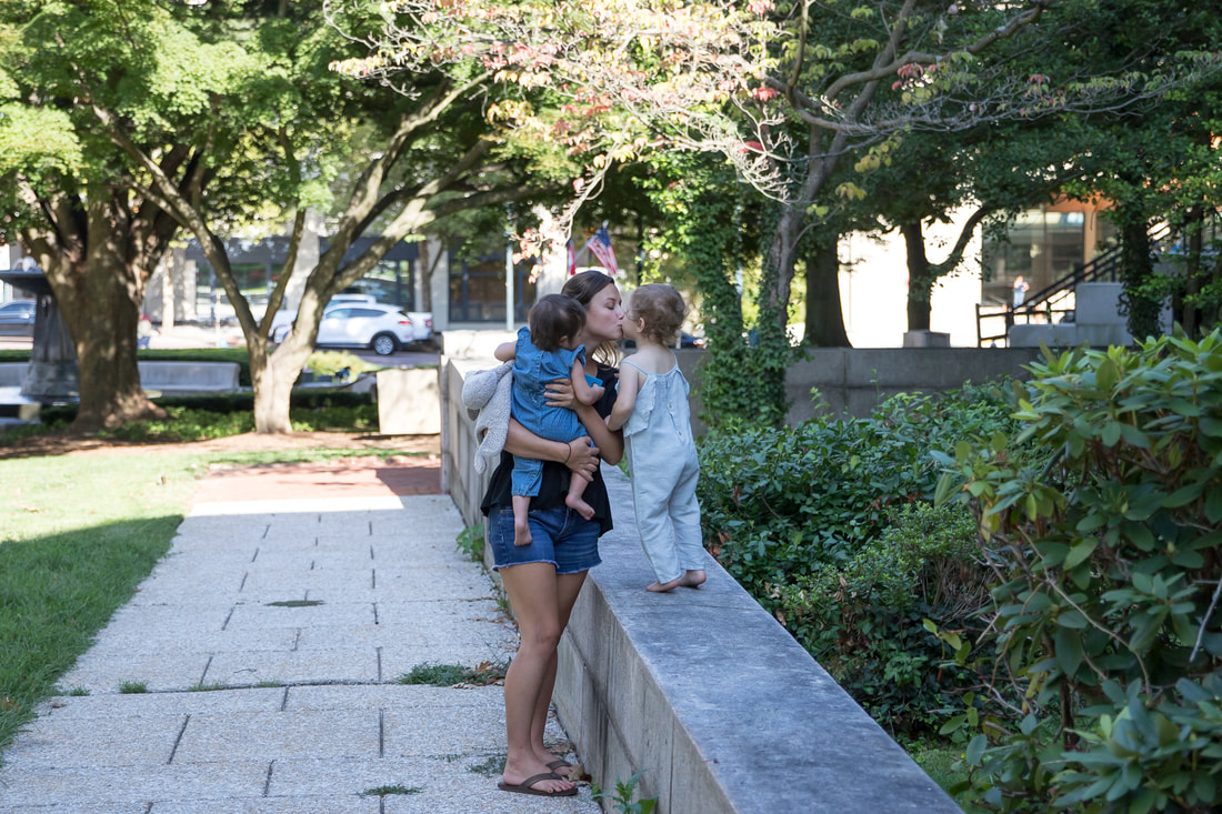 Lifestyle, mom holding toddler while kissing other toddler walking on wall, outdoors