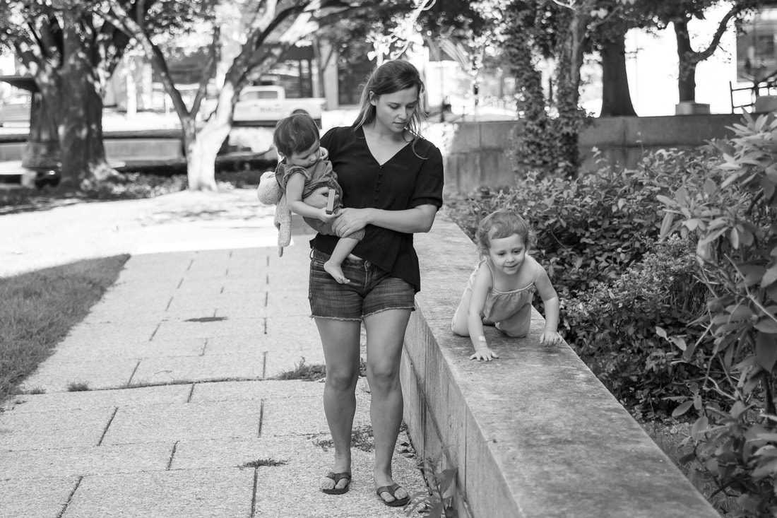 Lifestyle, black and white, mom holding toddler, sibling walking on a wall, outdoors