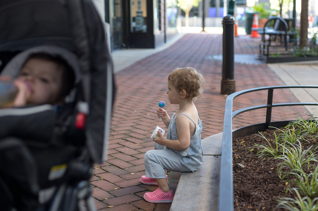 Lifestyle, toddler girl sitting on curb holding a lollypop, toddler girl in stroller, outdoors
